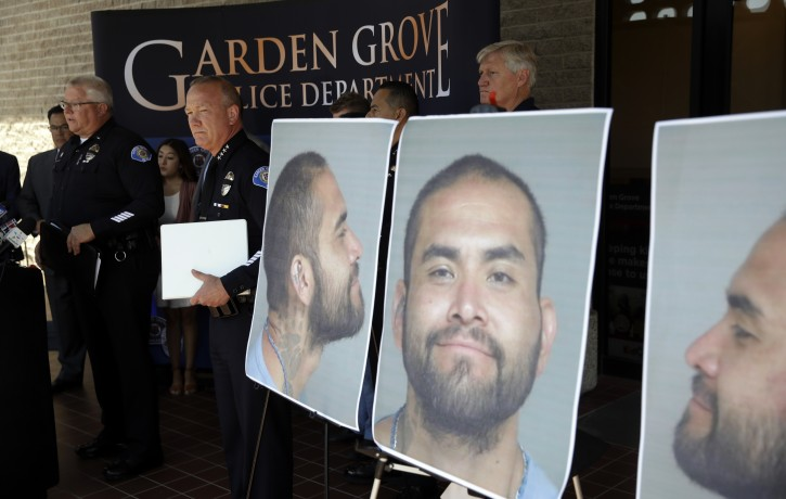 Garden Grove Police Chief Tom DaRe, center, and PIO Carl Whitney address the media next to a booking mug shot of Zachary Castaneda posted outside of the Garden Grove Police Department headquarters in Garden Grove, Calif., Thursday, Aug. 8, 2019. Investigators believe Castaneda, a documented gang member, stabbed several people to death and wounded a few others as he targeted his victims at random during a bloody rampage across two Southern California cities, authorities said. (AP Photo/Marcio Jose Sanchez)