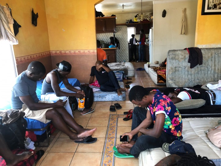 In this July 28, 2019, photo, Cameroonians wait in a rented apartment in Tijuana, Mexico, until their names are called to claim asylum in the U.S. The Cameroonian men who share 10 mattresses on the floor of a third-floor apartment above a barber shop walk every morning to the busiest U.S. border crossing with Mexico, hoping against all odds that it will be their lucky day to claim asylum. Their unlikely bet is that a sympathetic Mexican official will somehow find a spot for them. (AP Photo/Elliot Spagat)